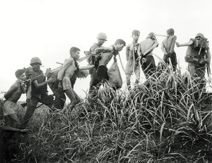 06 Nov 1965, Da Nang, South Vietnam --- 11/6/1965- Da Nang, South Vietnam- Viet Cong prisoners with their hands tied behind their backs are marched along in a small group where each man is joined to the other by cloth bands around the neck. A marine leads the Viet Cong on a halter during a marine operation from Da Nang. --- Image by © Bettmann/CORBIS